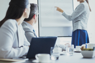 Businesswoman leading meeting at flip chart in conference room - CAIF08984