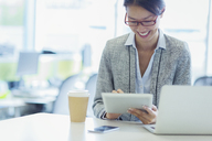 Smiling businesswoman using digital tablet with coffee in office - CAIF08990