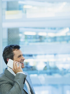 Smiling businessman talking on cell phone in office - CAIF09002