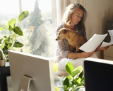 Woman with dog reviewing paperwork in sunny home office - CAIF09008