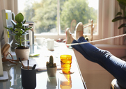 Woman talking on telephone with feet up on desk in sunny home office - CAIF09011