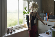 Young woman stretching at window in home office - CAIF09014