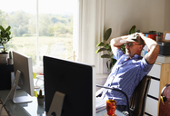 Man leaning back working at computer in sunny home office - CAIF09023