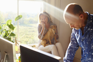Couple with dog in sunny home office - CAIF09026