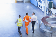 Workers in reflective clothing walking in factory - CAIF09032