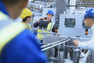 Workers talking at machinery in factory - CAIF09068