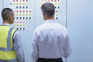 Supervisor and worker at control panel in factory - CAIF09077