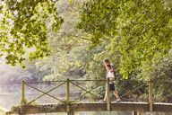 Father and son crossing footbridge in park with trees - CAIF09095