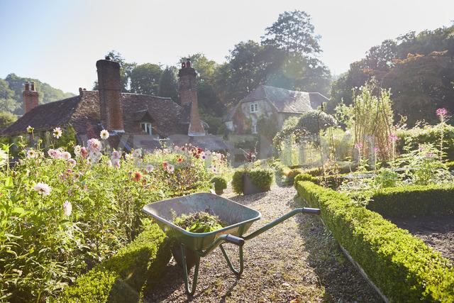 Wheelbarrow in sunny formal garden - CAIF09104