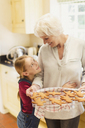 Granddaughter hugging grandmother baking gingerbread cookies - CAIF09107