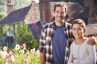 Portrait smiling father and son in sunny flower garden - CAIF09146