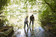 Father and son fishing with nets in forest pond - CAIF09164