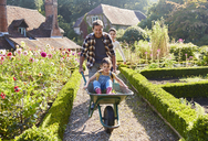 Father pushing daughter in wheelbarrow in sunny garden - CAIF09176