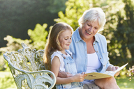 Grandmother reading with granddaughter on garden bench - CAIF09182