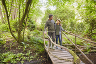Father and son crossing footbridge in forest - CAIF09197