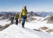Greenland, Sermersooq, Kulusuk, Schweizerland Alps, mountaineers walking in snowy mountainscape - ALRF00948