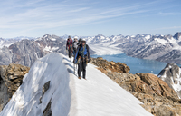 Greenland, Sermersooq, Kulusuk, Schweizerland Alps, mountaineers walking in snowy mountainscape - ALRF00951