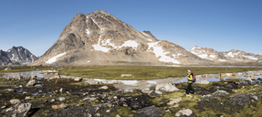 Greenland, Sermersooq, Kulusuk, Schweizerland Alps, woman walking at a brook - ALRF00954