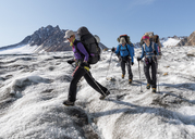 Greenland, Sermersooq, Kulusuk, Schweizerland Alps, three people walking in snowy mountainscape - ALRF00984