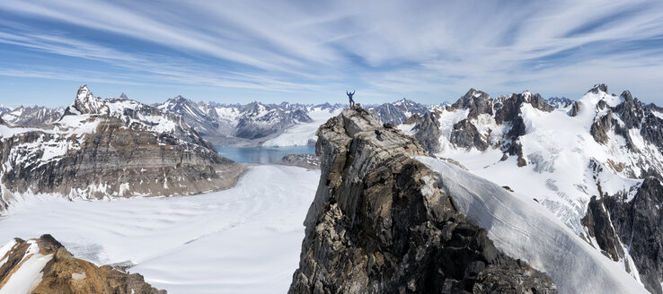 Greenland, Sermersooq, Kulusuk, Schweizerland Alps, mountaineer with raised arms on summit - ALRF01005