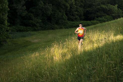 Man jogging on grassy field - CAVF04119