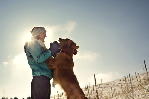 Low angle view of woman playing with dog against sky - CAVF04128