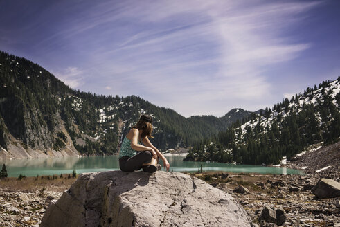 Side view of woman sitting on rock against mountain - CAVF04380