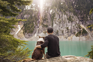Rear view of man sitting with dog on mountain against lake - CAVF04407