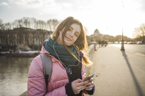 Paris, France, portrait of smiling young woman listening music with earphones and smartphone - AFVF00287