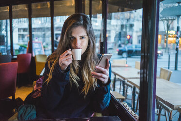 Paris, France, portrait of young woman with smartphone drinking espresso in a coffee shop - AFVF00293