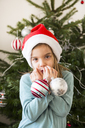 Portrait of little girl with Christmas baubles wearing Christmas cap - LVF06774
