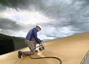 Austria, construction worker fixing medium-density fibreboard - CVF00270