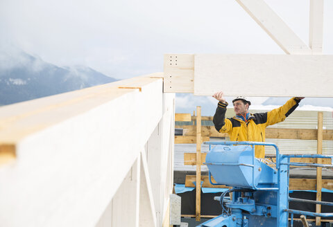 Austria, worker on hoist, positioning roof construction - CVF00276
