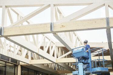 Austria, worker on hoist, roof construction - CVF00279