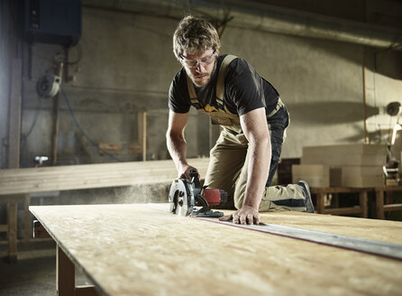 Carpenter sawing wood with handsaw - CVF00291