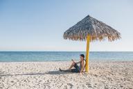 Cuba, Young man sitting under a sunshade at Playa Ancon - GUSF00543