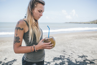Cuba, Young woman with tattoo at Playa de Miel drinking coconut water - GUSF00555