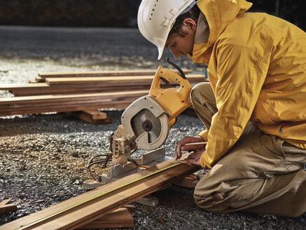 Man measuring decking board, circular saw - CVF00296