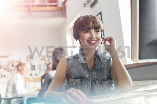 Smiling design professional using headset with microphone in office - CAIF09243