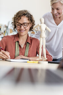 Female design professionals with artist's figure sketching in office - CAIF09270