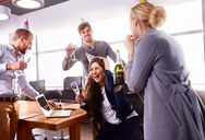 Business people drinking champagne, celebrating birthday in conference room - CAIF09294