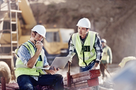 Foreman and construction worker using laptop at construction site - CAIF09306