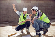 Construction worker and engineer talking at sunny construction site - CAIF09309
