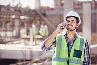 Construction worker talking on cell phone at sunny construction site - CAIF09318
