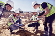 Construction workers and engineers using digital tablets at sunny construction site - CAIF09321