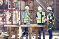 Construction workers and foreman talking at sunny construction site - CAIF09324