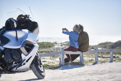 Senior couple taking selfie at sunny roadside near motorcycle - CAIF09333