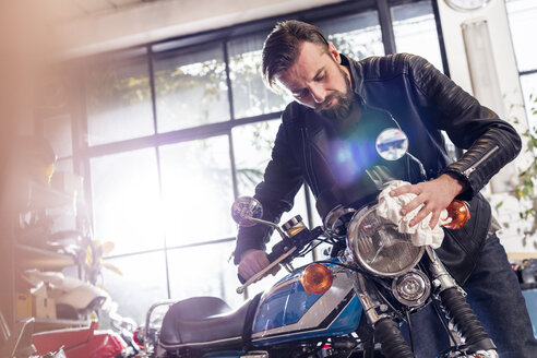 Male motorcycle mechanic wiping motorcycle in workshop - CAIF09372