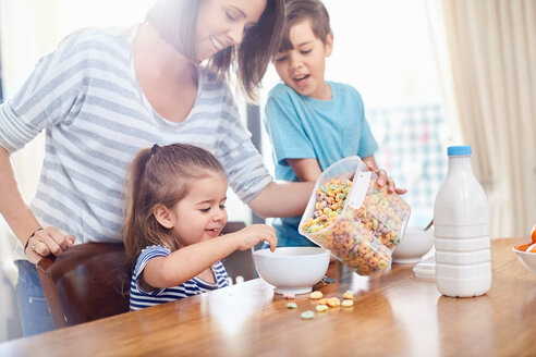 Mother pouring cereal for daughter at breakfast table - CAIF09378
