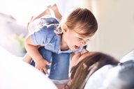 Playful mother holding laughing baby son on knees - CAIF09381